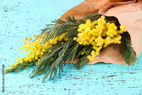 Twigs of mimosa flowers on old wooden table
