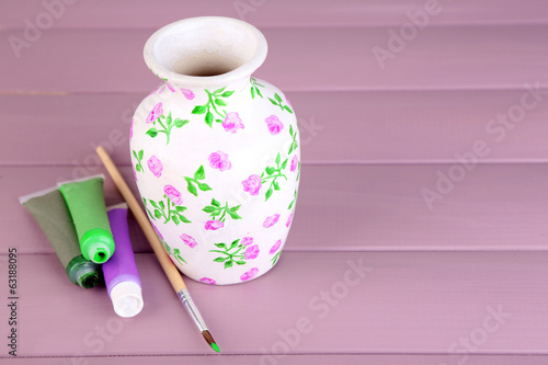 Beautiful hand made vase and art materials on wooden table