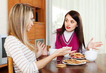 women having conflict over tea table