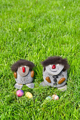 Zwei Steinmaennchen mit Ostereiern  im grünen Gras, hoch