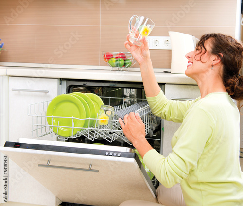 Dishwasher. Happy Young Woman in the Kitchen doing Housework