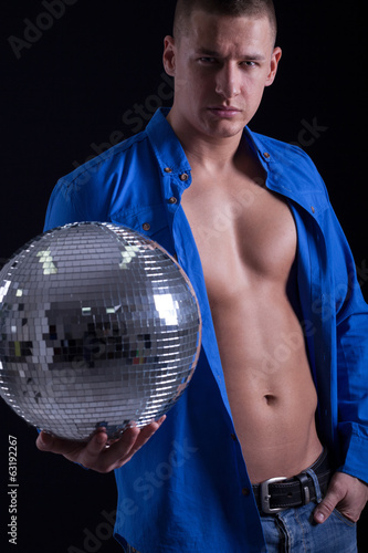 young sexy man holding a disco ball