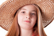 portrait of beautiful freckled young girl wearing straw hat