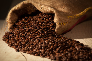 Coffee beans in burlap sack against dark wood