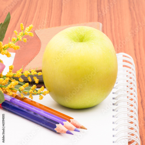 Green apple and crayon on the table.