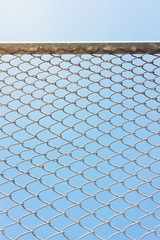 Wire fence with futsal field on background