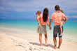 Back view of young beautiful family with two kids on tropical
