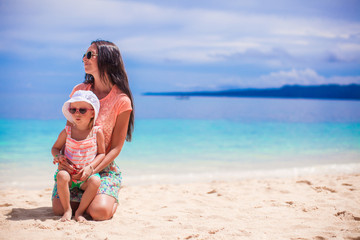 Adorable little girl and her mother on the white sandy beach
