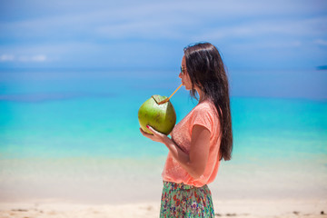 Young beautiful woman with a big coconut in hands drinking milk