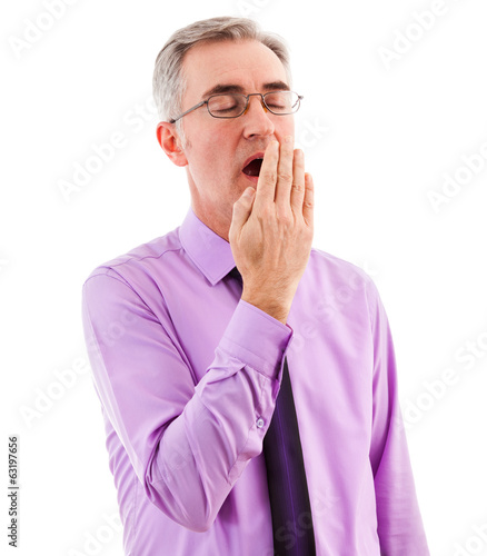 Sleepy businessman covering mouth and yawning