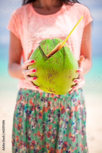 Closeup green big coconut in hands of young woman