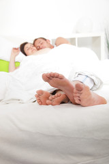Feet of a young couple sleeping in bed