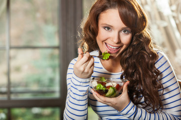 Woman eating fresh vegetable salad