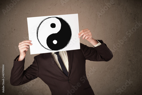 Businessman holding a paper with a yin-yang on it in front of hi