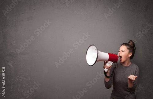Girl shouting into megaphone on copy space background - 63199233