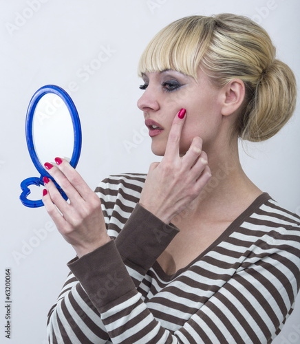 Portrait of beautiful woman applying anti-wrinkles cream