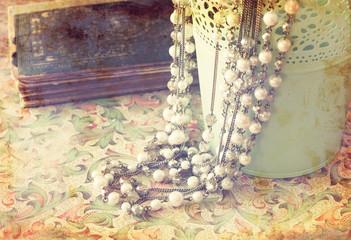 vintage pearl necklace over floral pattern background. retro fil