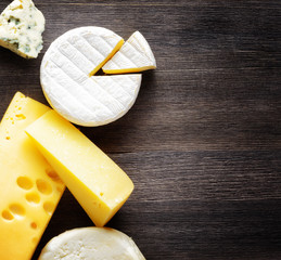 Different types of cheese on a wooden board