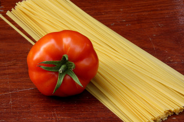 tomato and raw pasta on wooden table