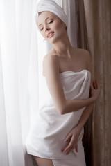 Sexy woman posing in towel, smiling at camera