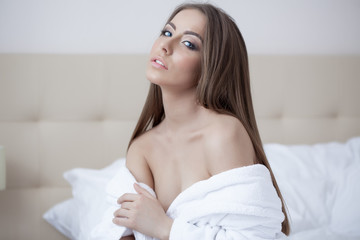 Sexy blue-eyed woman posing in hotel bedroom