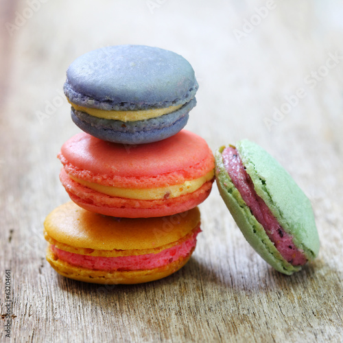 Colorful french macaroons stacked on wood table.