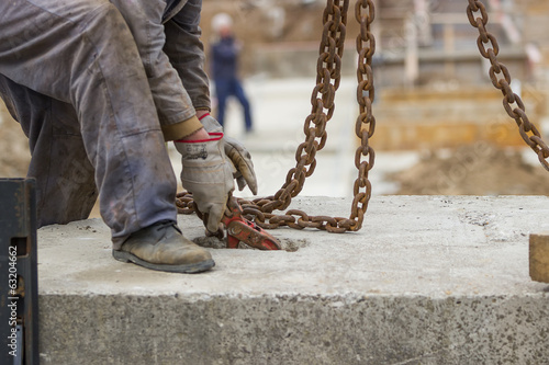 Builder worker preparing concrete profile for crane lifting