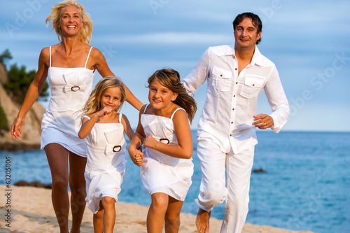 Dynamic family running on beach.