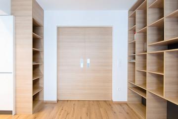 empty bookshelves and closed door in empty apartment