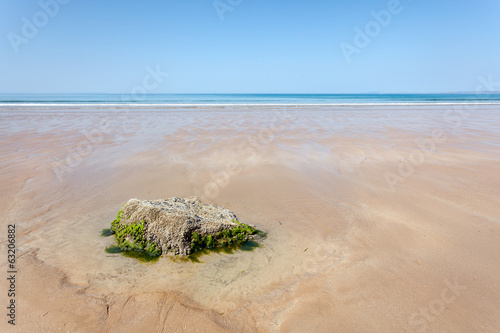 Minimal summer landscape : sandy beach, blue sea, clear sky