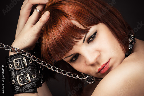 portrait of beautiful brown-haired woman in handcuffs