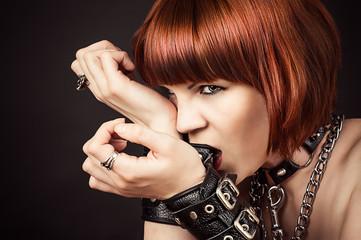 beautiful fashionable woman gnaws leather handcuffs
