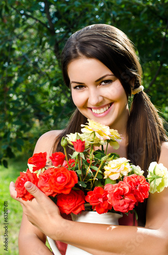 Girl in the garden with flowers,with a vase of red yellow roses.