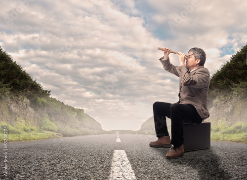 businessman looking through spyglass on a road
