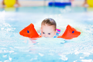 Cute toddler girl swimming in a pool with her face underwater