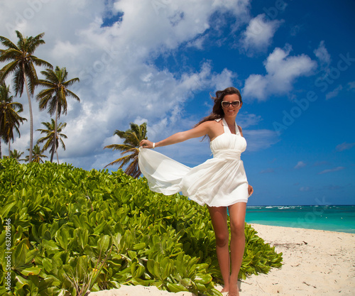 Young beautiful female model in white dress on Caribbean beach