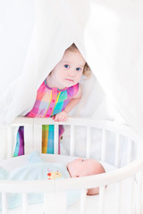Funny curly toddler girl hiding from her newborn baby brother