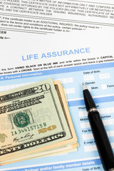 Life assurance application form with pen and banknote concept fo