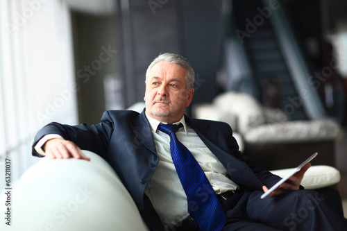 Portrait of a mature businessman with digital tablet