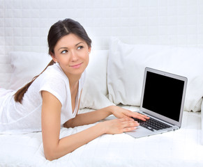 successful woman lying on a sofa with laptop paying bills