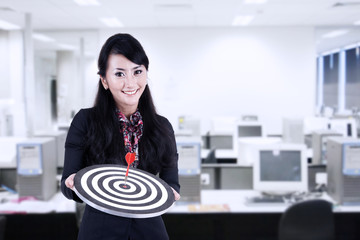 Businesswoman hold bull's eye at office