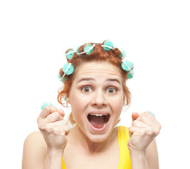 funny portrait of redheaded girl in hair curlers, isolated on wh