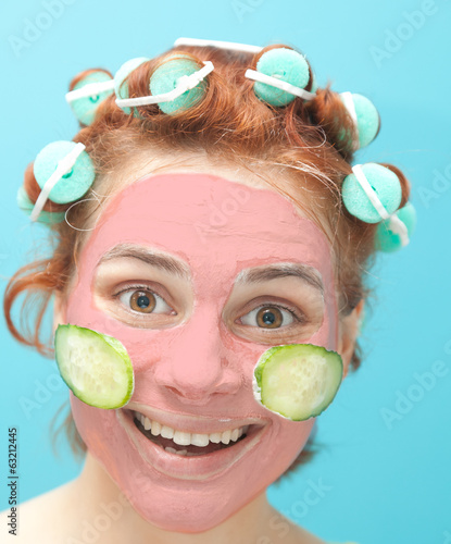 cute young woman in curlers and with a mask on her face on a blu