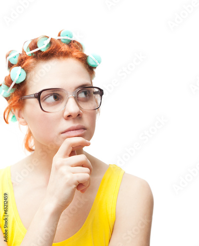thoughtful young woman in curlers isolated on white background
