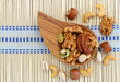 Selection of mixed nuts in wooden bowl on bamboo mat