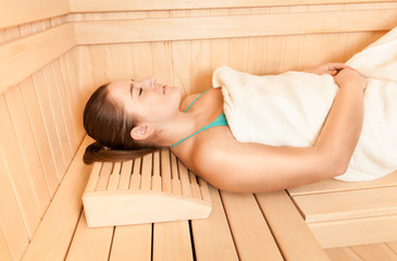 woman lying with closed eyes at steam bath