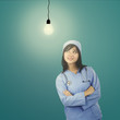Female surgeon looking at light bulb