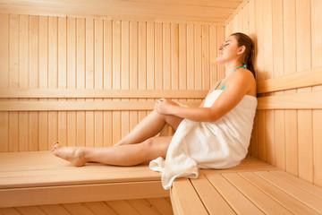 Beautiful woman lying on bench at scandinavian sauna
