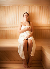 Beautiful young woman in towel relaxing at sauna