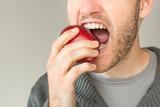 Fototapety Closeup of man with beard biting an apple